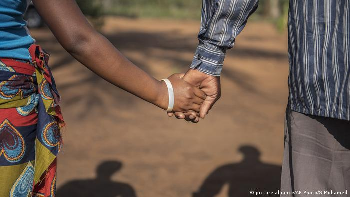 A man and a woman hold hands (picture alliance/AP Photo/S.Mohamed)