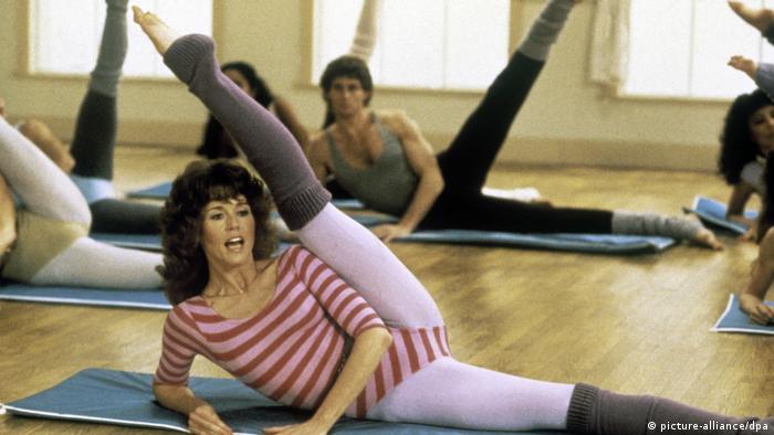 Jane Fonda beim Aerobic, sie liegt auf dem Boden und streckt das Bein