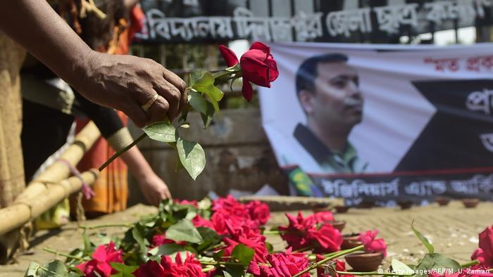 Ein Mann legt eine rote Rose zu vielen weiteren Rosen, die vor dem Porträt des ermordeten Bloggers Avijit Roy aufgereiht wurden. (Foto: Getty Images/AFP/M. U. Zaman)