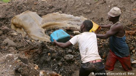Two young men pour water from a mine in the east Congolese province of South Kivu.