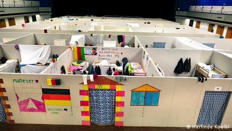 Τα καταλύματα που στήθηκαν προσωρινά στο γερμανικό κέντρο υποδοχής μοιάζουν σα μικρά κελιά, τα οποία συνδέονται σε ένα μεγαλύτερο δίκτυο από κατοικίες. Εδώ, όμως, μπορεί κανείς να έχει τουλάχιστον ιδιωτική ζωή συγκριτικά με τα ανάμεικτα προσωρινά κέντρα με σκηνές στην Ελλάδα ή στη ΠΓΔΜ, όπως λέει η Κολμπλ.