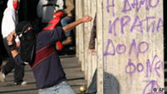 A masked protestor throws a stone next to graffiti that reads the democracy kills, in central Athens