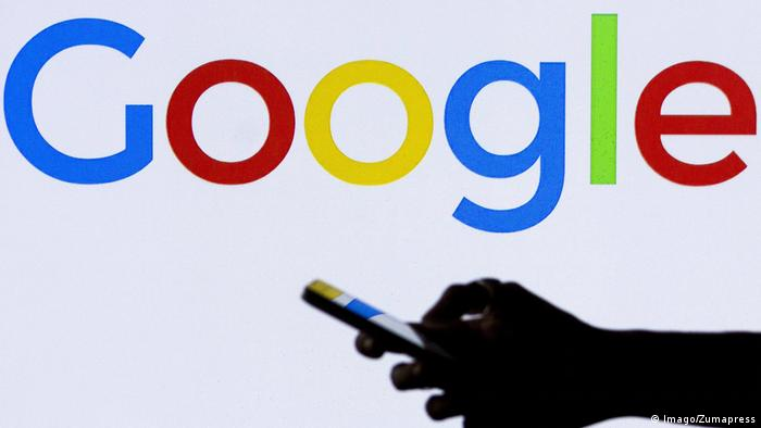 Google logo as seen on a TV behind a smartphone