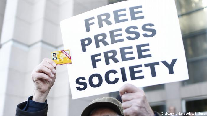 A protester in Turkey holding a sign that reads Free Press Free Society