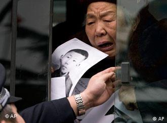 Un policía impide que un manifestante proteste por las violaciones a los DD.HH. en China.
