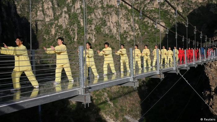 People practice Taichi on a suspension bridge during an event at a tourist spot in Beijing (Reuters)