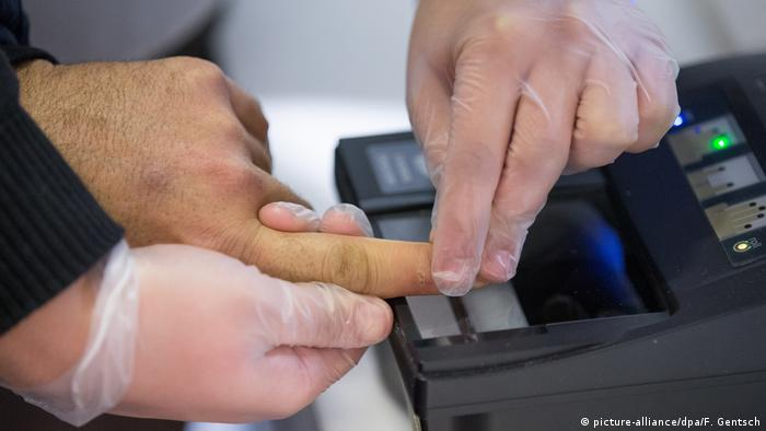 A person having an index finger scanned (picture-alliance/dpa/F. Gentsch)