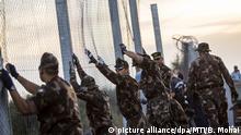 ARCHIV - Ungarische Soldaten errichten am 14.09.2015 in Röszke an der Grenze zwischen Serbien und Ungarn einen Zaun. Die Balkanroute ist unterdessen für Migranten weitgehend geschlossen. In Griechenland sitzen viele fest. (zu dpa Balkanroute geschlossen - Schleuser machen weiter gute Geschäfte vom 23.02.2017) Foto: Balazs Mohai/MTI/dpa +++(c) dpa - Bildfunk+++ |