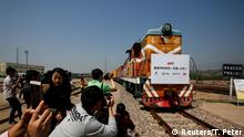 People take pictures as a train carrying containers from London arrives at the freight railway station in Yiwu, Zhejiang province, China, April 29, 2017. The sign at the front of the train reads: First Sino-Euro Freight Train (London Yiwu). REUTERS/Thomas Peter