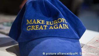 A blue baseball cap with the word Make Europe Great Again lies on a desk