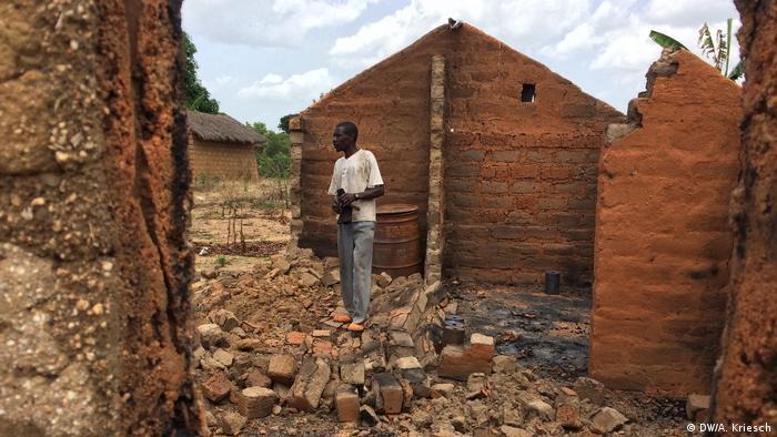 A man stands inside a burnt house.