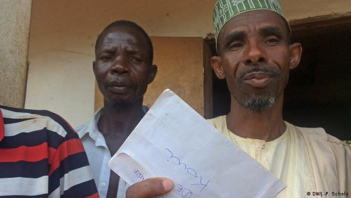 A Muslim man holds a letter as other men look on. (DW/J.-P. Scholz)