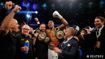 Anthony Joshua celebrates with trainer Robert McCracken and promoter Eddie Hearn after winning the fight (REUTERS)