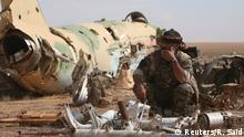 A Syrian Democratic Forces (SDF) fighter rests near destroyed airplane parts inside Tabqa military airport after taking control of it from Islamic State fighters, west of Raqqa city, Syria April 9, 2017. REUTERS/Rodi Said