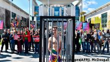 30.04.2017 +++ An activist stands naked, wrapped in a rainbow flag, in a mock cage in front of the Chancellery in Berlin on April 30, 2017, during a demonstration calling on Russian President to put an end to the persecution of gay men in Chechnya. The protestors called on German Chancellor Angela Merkel, who will meet Putin in Sochi on May 2, 2017, to raise the issue with him. / AFP PHOTO / John MACDOUGALL (Photo credit should read JOHN MACDOUGALL/AFP/Getty Images)