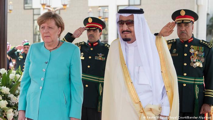Saudi Arabia's King Salman bin Abdulaziz Al Saud stands next to German Chancellor Angela Merkel during a reception ceremony in Jeddah