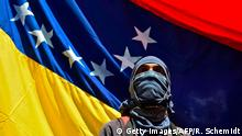 TOPSHOT - A man attends a march paying homage to student Juan Pablo Pernalete -killed on the eve by impact of a gas grenade during a protest against President Nicolas Maduro- in Caracas, on April 27, 2017. Venezuela defied international pressure over its deadly political crisis as European lawmakers accused its government of brutal repression and US President Donald Trump called the country a mess. Nearly a month of clashes at anti-government protests have left 28 people dead, according to prosecutors. / AFP PHOTO / RONALDO SCHEMIDT (Photo credit should read RONALDO SCHEMIDT/AFP/Getty Images)