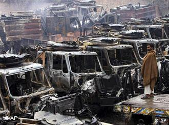 A man looks at Afghanistan-bound vehicles gutted by alleged militants on the outskirts of Peshawar, Pakistan