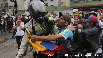 A protester scuffles with police during a May Day opposition march in eastern Caracas (AP Photo/Fernando Llano)