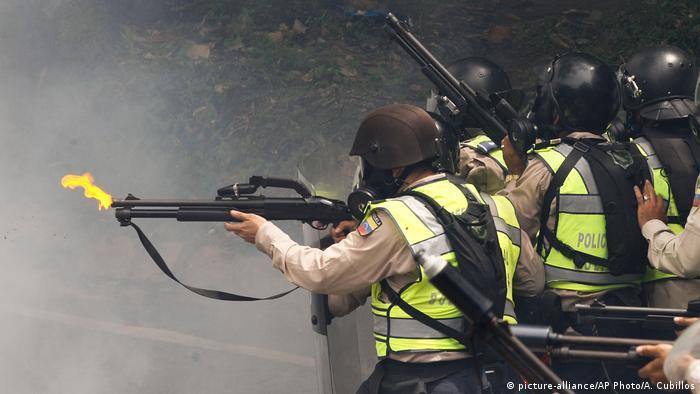 Agentes policiales lanzan gases lacrimógenos contra manifestantes.