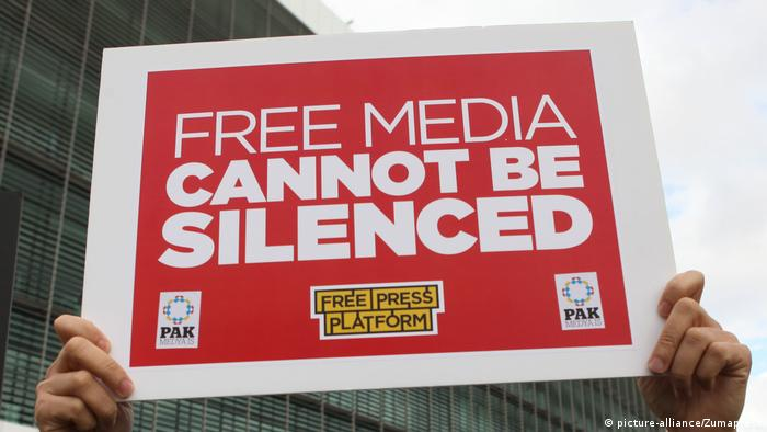 A red-and-white poster that reads 'Free media cannot be silenced' (picture-alliance/Zumapress)