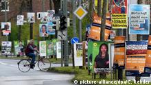 A cyclist in northern Germany turns into a road lined with green, orange and blue campaign posters