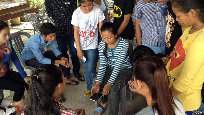 Several young people are grouped around a young Cambodia woman holding a smart phone