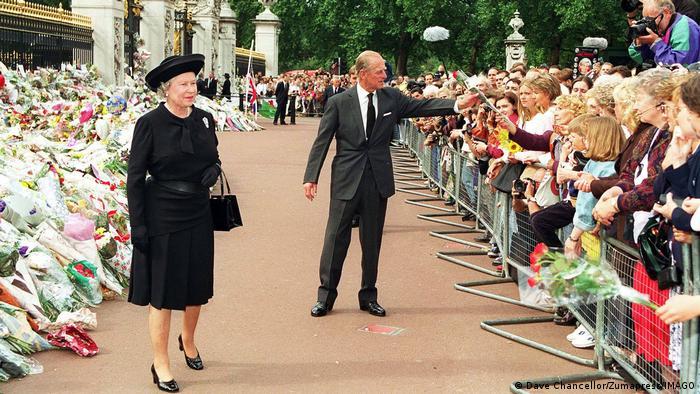 Queen Elizabeth und Prinz Philip vor den Blumen am Palast für Lady Di, hinter einem Geländer eine Menschenmenge