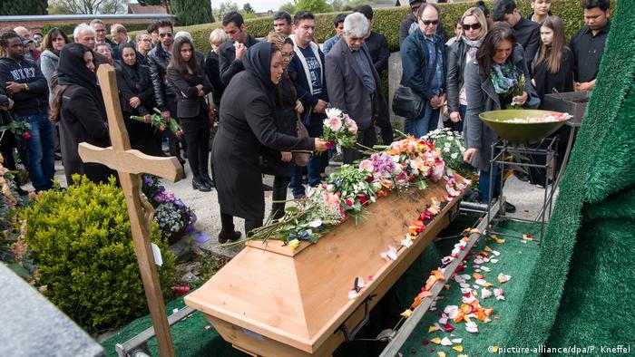 People laying flowers on the victim's coffin (picture-alliance/dpa/P. Kneffel)