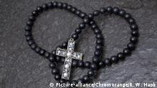 schwarze Perlenkette mit Kruzifix auf Ölschieferplatte