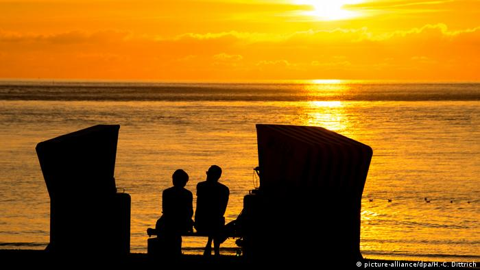 Two people enjoying sunset on the beach