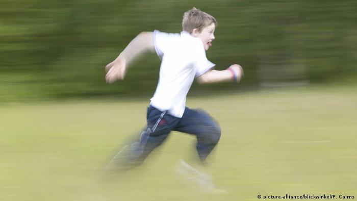 Symbolbild: Ein Junge in schwarzer Hose und weißem kurzen Hemd und herausgestreckter Zunge rennt über eine Wiese, so als ob er sehr schnell irgendwohin kommen möchte