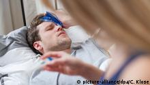 man lying sick in bed (picture-alliance/dpa/C. Klose)