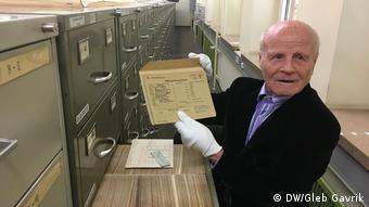 Александр Афанасьев держит в руках свою регистрационную карту из Бухенвальда
