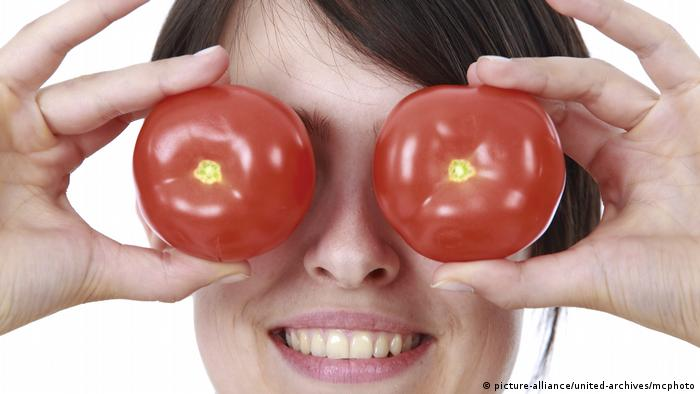 Woman holding tomatoes in front of her eyes (picture-alliance/united-archives/mcphoto)