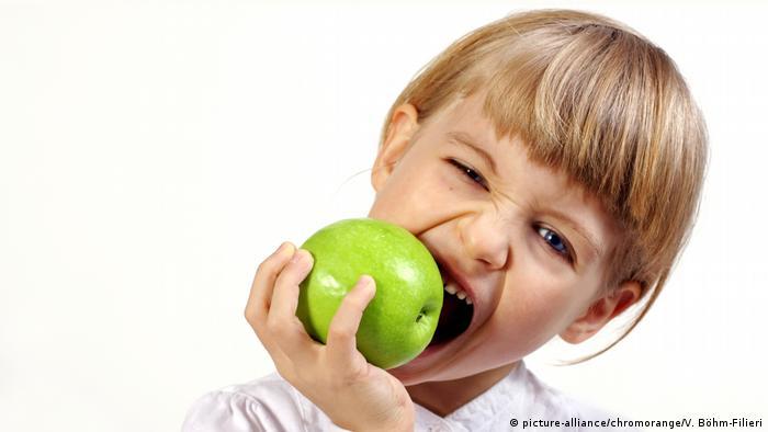 Ein kleines Mädchen beißt in einen grell-grünen Apfel.