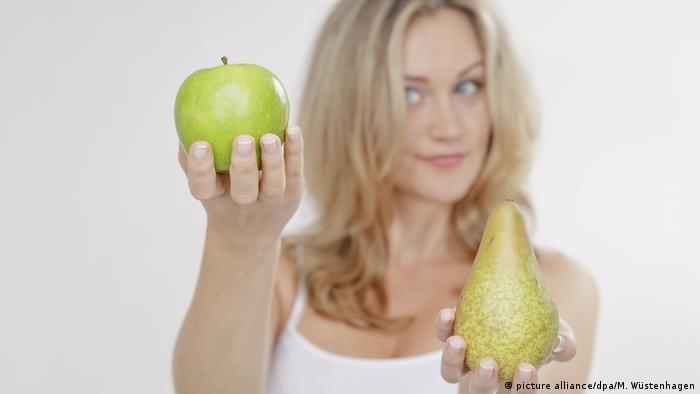 Eine Frau hält in ihrer einen Hand einen Apfel, in der anderen eine Birne hoch.