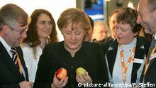 Die CDU-Vorsitzende und Bundeskanzlerin Angela Merkel schaut sich am Montag (03.12.2007) auf dem Messegelände in Hannover auf dem CDU-Bundesparteitag einen Apfel und eine Birne an, rechts neben ihr Magdalene Linz, Präsidentin der Bundesapothekenkammer und Heinz-Günther Wolf, Präsident der ABDA (Bundesvereinigung Deutscher Apothekerverbände). Bis zum 04.12.2007 tagen hier rund 1000 Delegierte und werden unter anderem das dritte Grundsatzprogramm beschließen. Foto: Peter Steffen +++(c) dpa - Report+++ | Verwendung weltweit