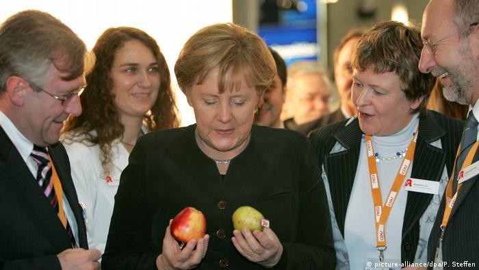 Ангела Меркель держит в руках яблоко и грушу