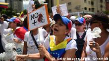 Venezuelan opposition activists take part in a women's march aimed to keep pressure on President Nicolas Maduro, whose authority is being increasingly challenged by protests and deadly unrest, in Caracas on May 6, 2017. The death toll since April, when the protests intensified after Maduro's administration and the courts stepped up efforts to undermine the opposition, is at least 36 according to prosecutors. / AFP PHOTO / RONALDO SCHEMIDT (Photo credit should read RONALDO SCHEMIDT/AFP/Getty Images)