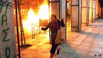 A woman runs during clashes between riot police and protesters in Athens on Dec. 13, 2008
