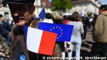 Mit einer Europafahne und einer Fahne in den französischen Nationalfarben an seiner Jacke nimmt ein Mann am 07.05.2017 in Potsdam (Brandenburg) an einer Kundgebung der Bewegung Pulse of Europe teil. Foto: Ralf Hirschberger/dpa-Zentralbild/dpa | Verwendung weltweit