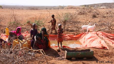 Two women sitted next to a water reservoir with three children and two goats around them