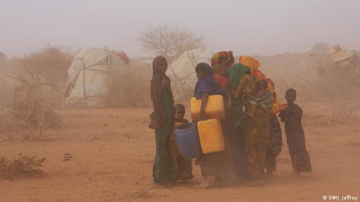 Some women holding empty water cotainers, together with their children, are protecting themselves from the sand