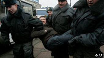 Russian city police officers detain an opposition demonstrator during an anti-Kremlin protest in St.Petersburg