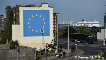 An artwork attributed to street artist Banksy, depicting a workman chipping away at one of the 12 stars on the flags of the European Union