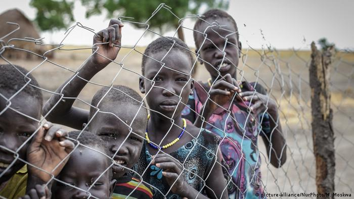 Children in South Sudan peer through a fence