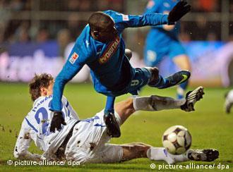 Zwei Fußballspieler, einer im weißen, einer im blauen Trikot, kämpfen um den Ball und fallen hin