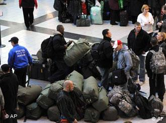 Stranded travelers stand by their baggage wait in a terminal of Ferihegy Airport in Budapest