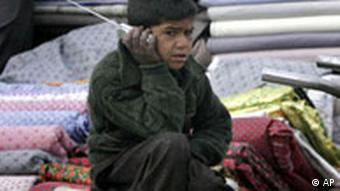 An Afghan street vender boy listens to his radio in the city of Kabul